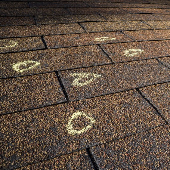 shingle roofing with chalk circles indicating storm damage