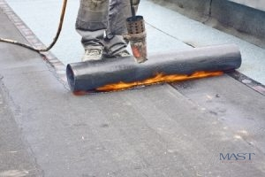 Roofer from a Commercial Roofing Company Fixing a Flat Roof