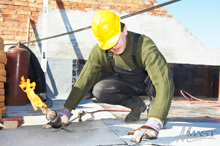 Roofer Preparing Part of Bitumen Roof Felt With Melting by Torch Flame
